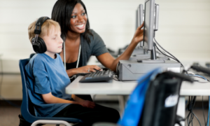 Teacher with special needs students working on computer together